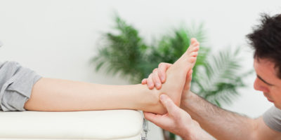 Close-up of a doctor massaging a foot in a room